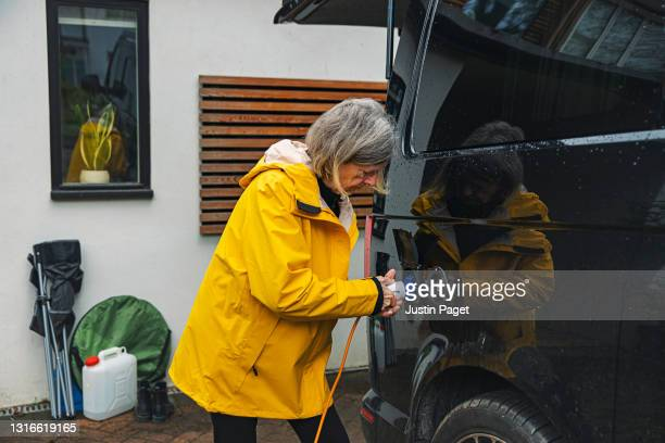 senior woman plugging the electricity into her campervan - one senior woman only stock pictures, royalty-free photos & images