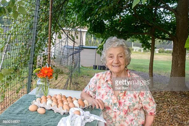 Senior woman posing beside tray of eggs on farm