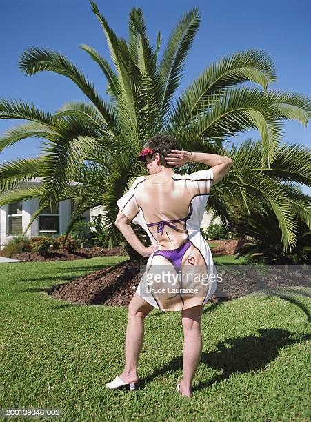 Senior woman posing in novelty t-shirt, rear view