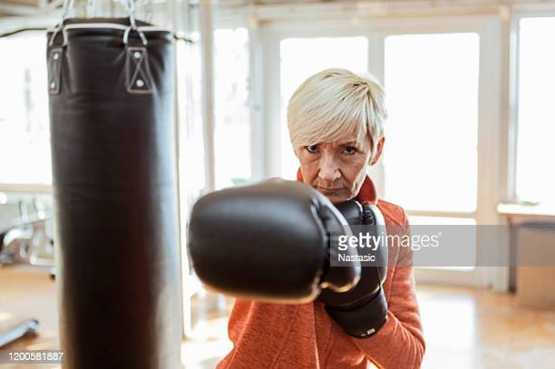 donna anziana in posa durante la boxe - sport da combattimento foto e immagini stock
