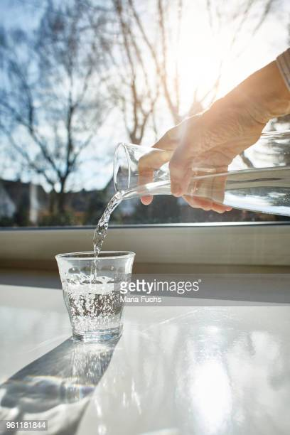 Senior woman pouring glass of water, close-up