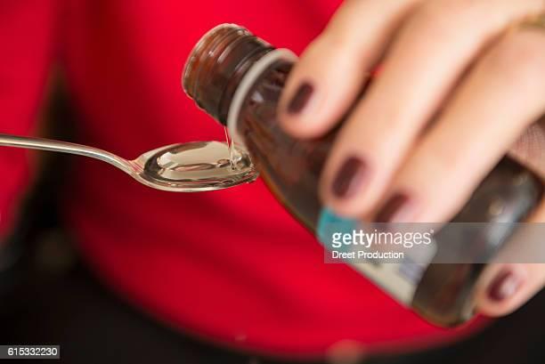 Senior woman pouring liquid medicine in a spoon, Munich, Bavaria, Germany
