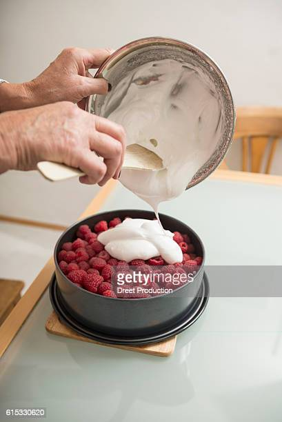 Senior woman pouring meringue on cake base and berries in springform pan, Munich, Bavaria, Germany