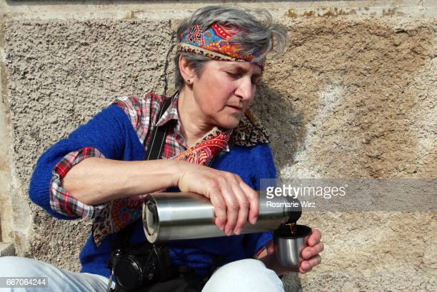 Senior woman pouring tea from thermos, sunshine, outdoors.