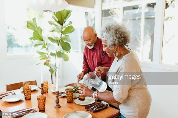 senior woman pouring water in glass by husband - drinking water stock pictures, royalty-free photos & images