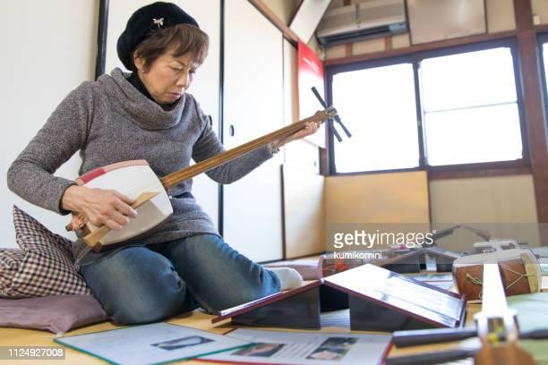 senior woman practice shamisen - vangen imagens e fotografias de stock
