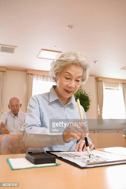 Senior woman practicing calligraphy, smiling
