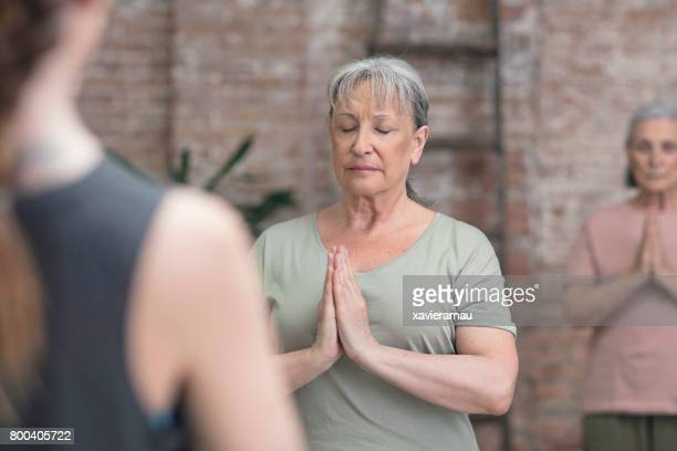 Senior woman practicing yoga in prayer position