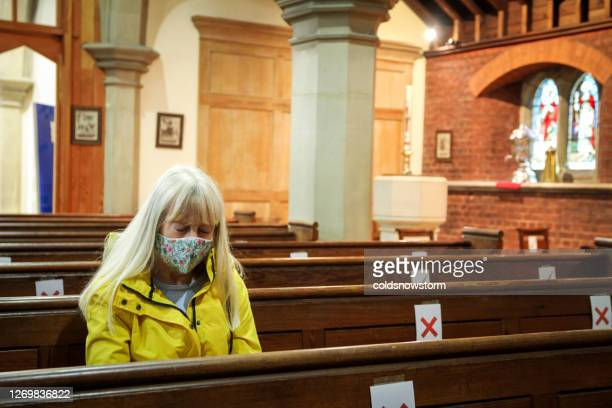 senior woman praying in church wearing protective face mask - church stock pictures, royalty-free photos & images