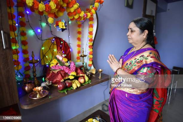 senior woman praying to hindu god lord ganesha - hinduism bildbanksfoton och bilder