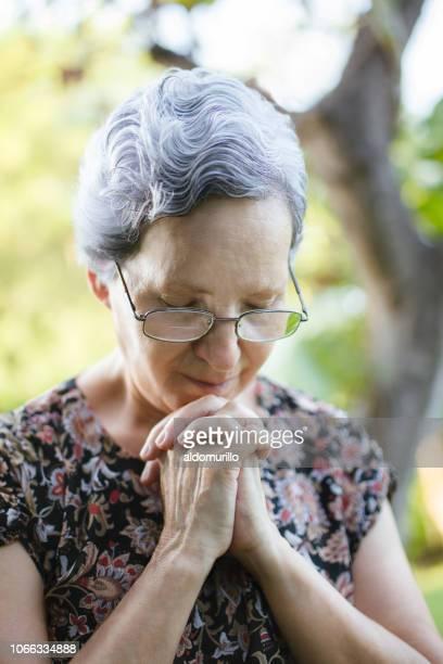 senior mulher rezando com as mãos e os olhos fechados - religião - fotografias e filmes do acervo