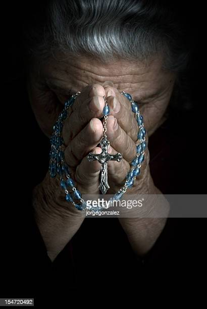 senior woman praying with rosary - rosary beads stock pictures, royalty-free photos & images