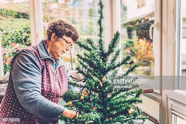 Senior Woman Preparing Christmas Tree on Balcony, Slovenia, Europe