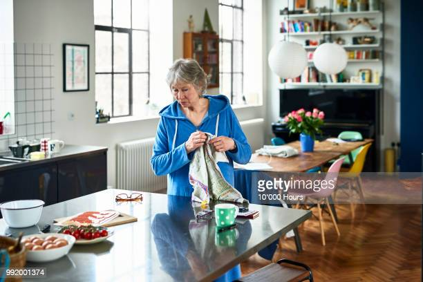 senior woman preparing food at kitchen island - dish towel stock pictures, royalty-free photos & images