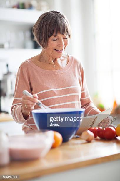 Senior woman preparing food from recipe book