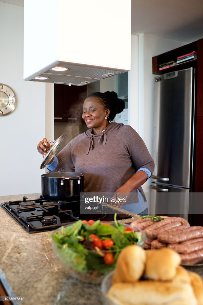 Senior woman preparing food on a gas stove lifting pot lid smelling the food : Stock Photo