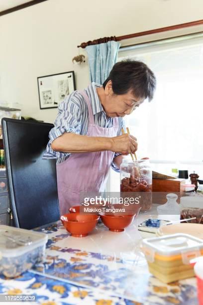 senior woman preparing for lunch on the table - makiko tanigawa ストックフォトと画像