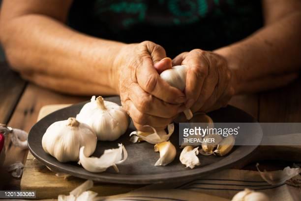 senior woman prepping garlic - garlic stock pictures, royalty-free photos & images