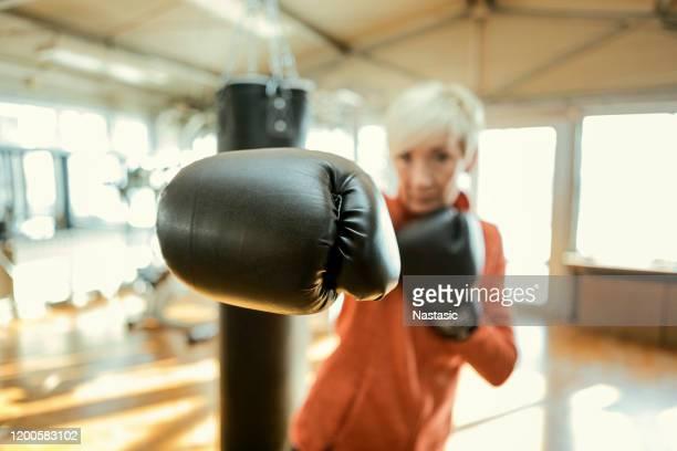 donna anziana che prende a pugni l'aria, guanto da boxe a fuoco - sport da combattimento foto e immagini stock