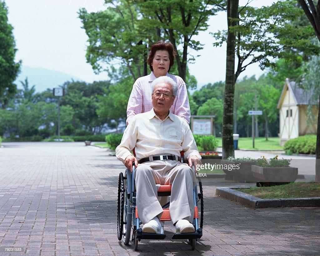 A senior woman pushing a senior man in a wheel chair : Stock Photo