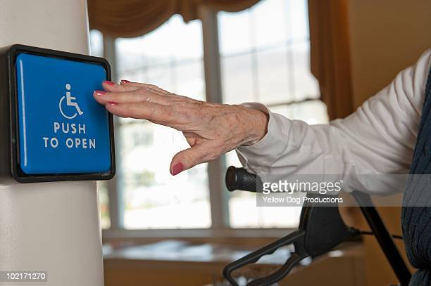 senior woman pushing automatice door opener - assistive technology stock photos and pictures