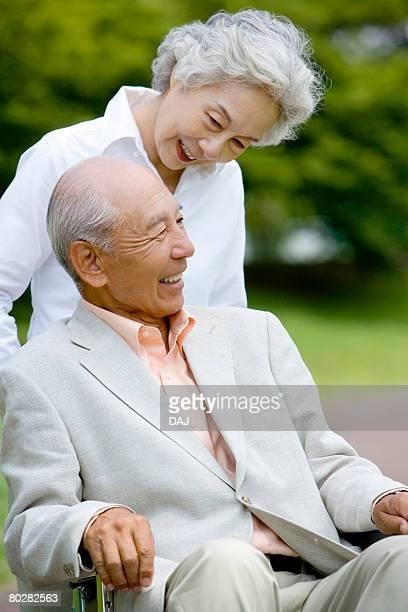Senior woman pushing senior man in wheelchair, smiling, differential focus