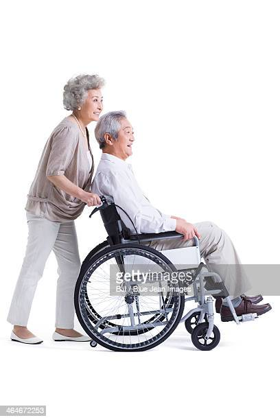 Senior woman pushing wheelchair bound husband