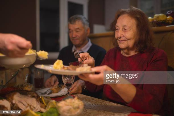 senior woman putting food on a plate during thanksgiving dinner - free thanksgiving stock pictures, royalty-free photos & images