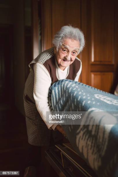 senior woman putting fresh sheets on a bed - tidy room stock pictures, royalty-free photos & images