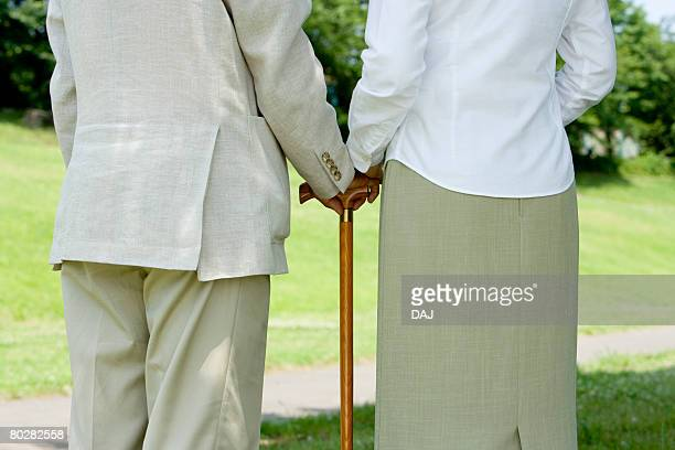 Senior woman putting hand on senior man's hand holding a stick