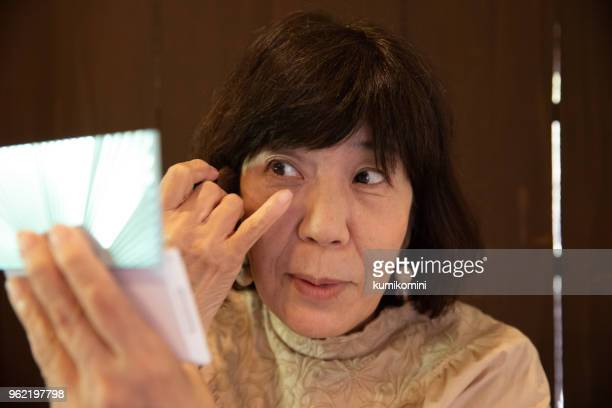 年配の女性が化粧をかけること - しわ ストックフォトと画像