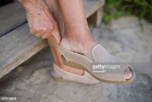 senior woman putting on shoe - old lady feet stock pictures, royalty-free photos & images