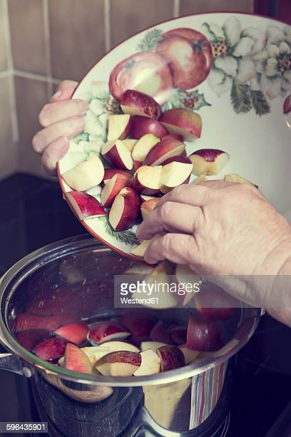 Senior woman putting pieces of apples in a cooking pot for preparing applesauce