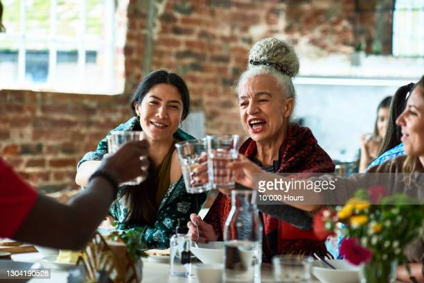 senior woman raising glass of water with friends - vacations stock pictures, royalty-free photos & images