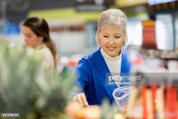 senior woman reaches for produce at grocery store - produce aisle stock photos and pictures