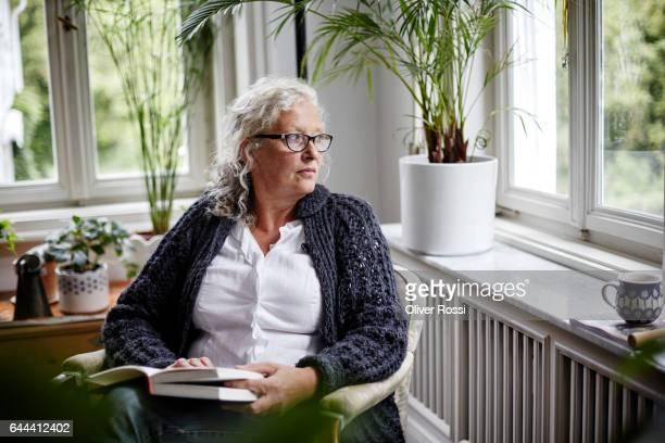 Senior woman reading a book at home