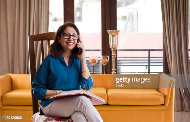 senior woman reading a book - south asia stock pictures, royalty-free photos & images