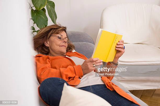 senior woman reading a book while lying on sofa at home, munich, bavaria, germany - alleen één seniore vrouw stockfoto's en -beelden
