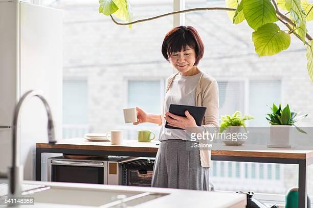 Femme âgée lisant une tablette numérique