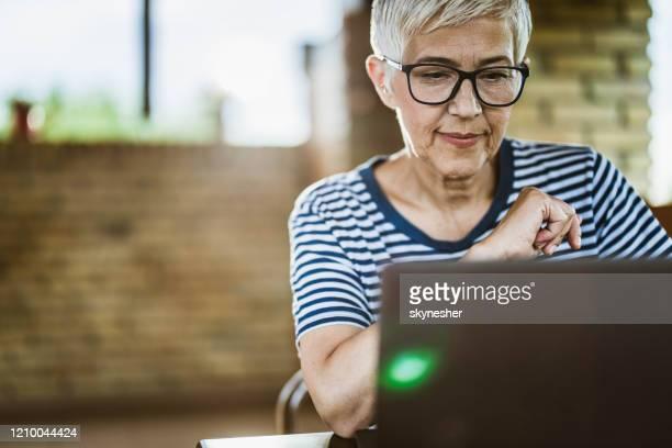 hogere vrouw die een e-mail op een computer leest. - alleen één seniore vrouw stockfoto's en -beelden