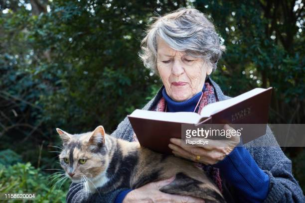 senior woman reading bible in her beautiful garden - compassionate eye stock pictures, royalty-free photos & images