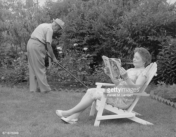 senior woman reading book and man working in garden - {{ contactusnotification.cta }} stockfoto's en -beelden