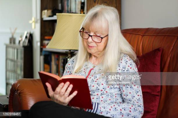 senior woman reading book in cosy home environment - reading glasses stock pictures, royalty-free photos & images