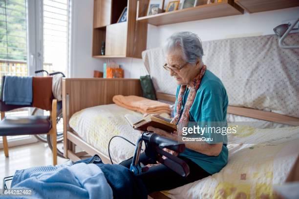 Senior Woman Lesebuch In ihrem Schlafzimmer in der alten Mitte