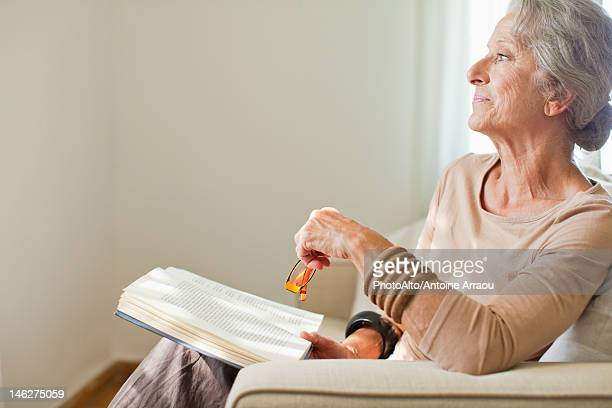 senior woman reading book on sofa - alleen één seniore vrouw stockfoto's en -beelden