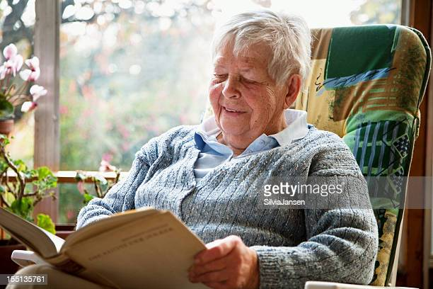 senior woman reading book - fat old women stock pictures, royalty-free photos & images