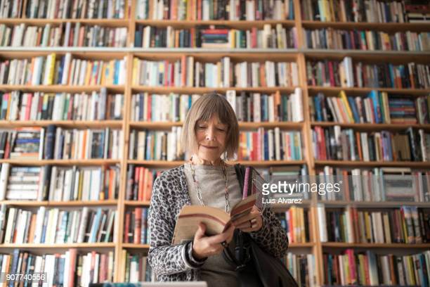 senior woman reading book while standing against bookshelf - hobbies stock pictures, royalty-free photos & images