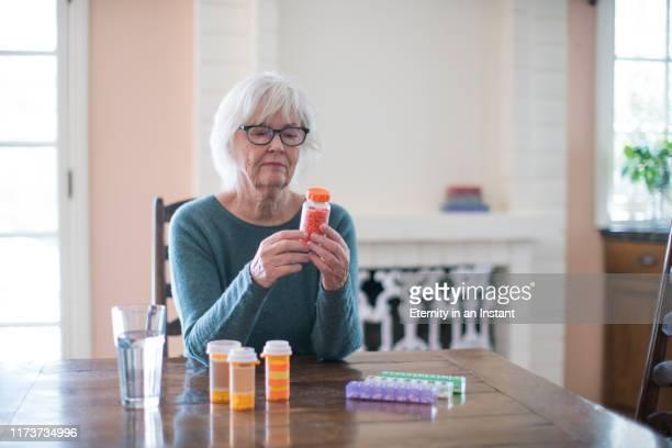 senior woman reading her medicine bottle - medicijnen innemen stockfoto's en -beelden