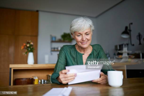 senior woman reading letter while sitting at home - mail stock pictures, royalty-free photos & images