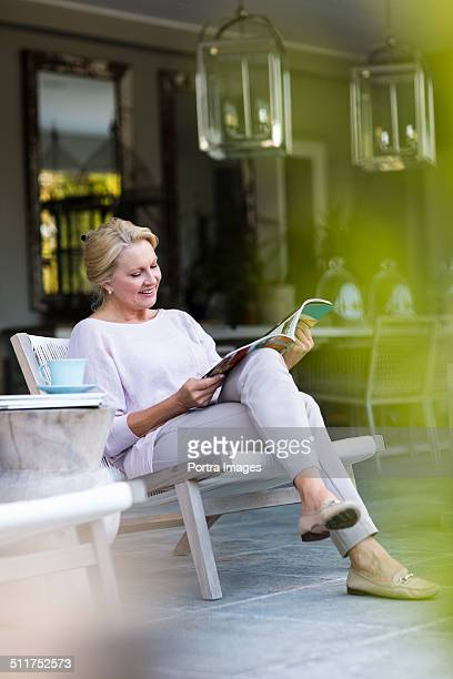 Senior woman reading magazine at porch
